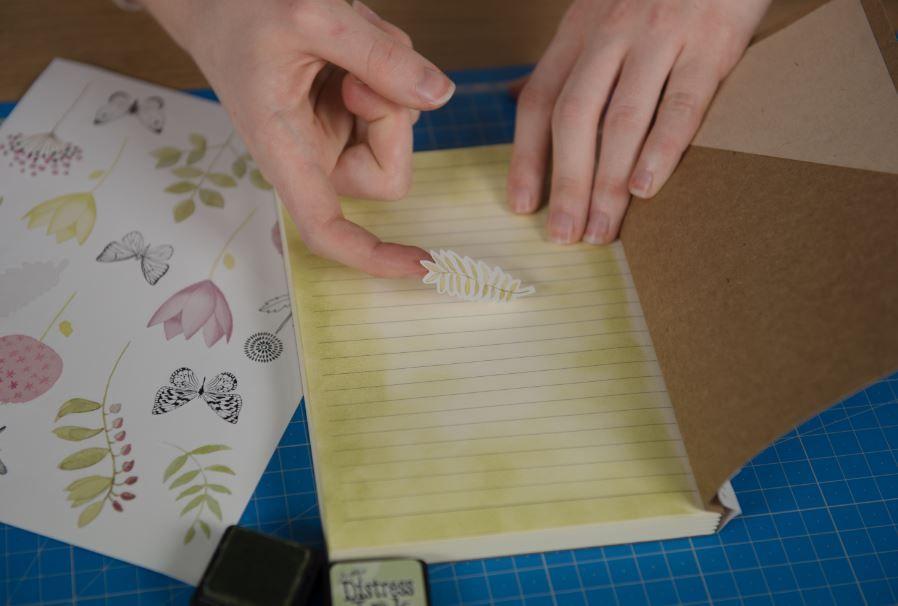 7. Enduire l'éponge à doigt d'encre Distress et appliquer en dégradé l'encre sur le contour des pages. Décorer avec des stickers de la collection.