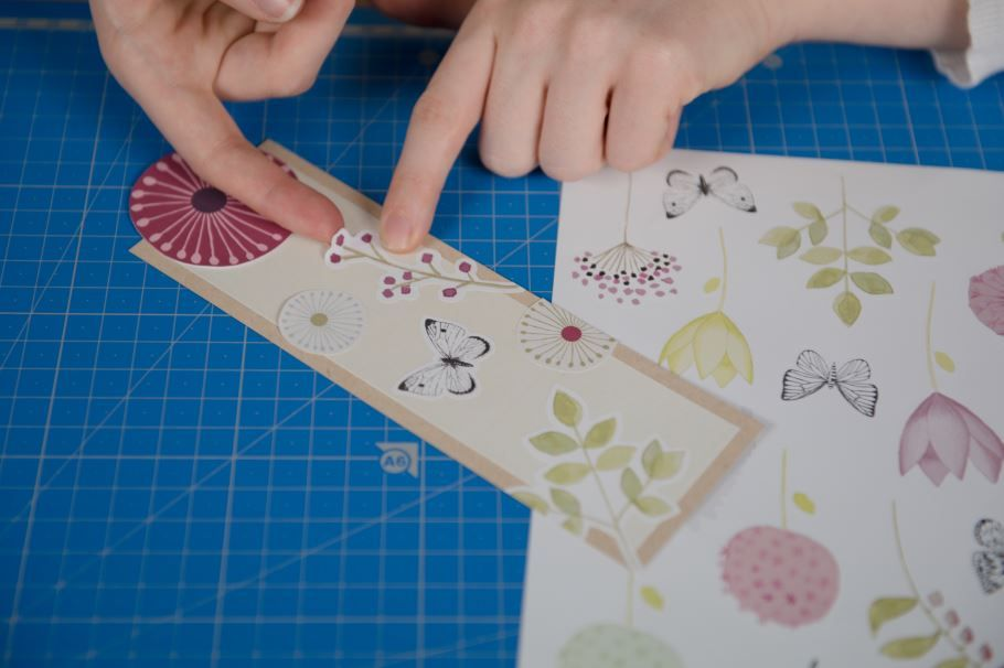 8. Découper un rectangle de papier kraft et superposer un rectangle de papier uni dont les dimensions seront réduites de 1 cm. Coller quelques stickers. Découper des fleurs rondes dans le papier de la collection et coller la plus grosse en haut du marque-page pour qu'elle déborde de moitié.