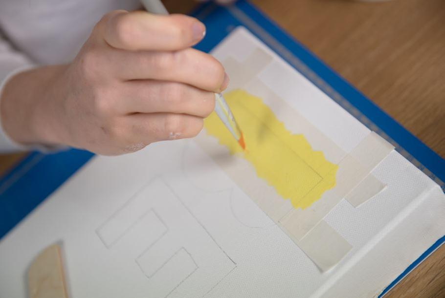 6. À l'aide du gabarit, reporter le mot « BE » sur la toile. Délimiter les zones des lettres à peindre à l'aide de ruban de masquage. Peindre les lettres de différentes couleurs. Laisser sécher.