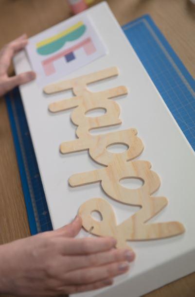 5. Appliquer une couche de gesso sur toute la toile. Laisser sécher. Définir le positionnement des éléments sur la toile en utilisant le gabarit du mot « BE » et la partie arrière du mot « Happy ».