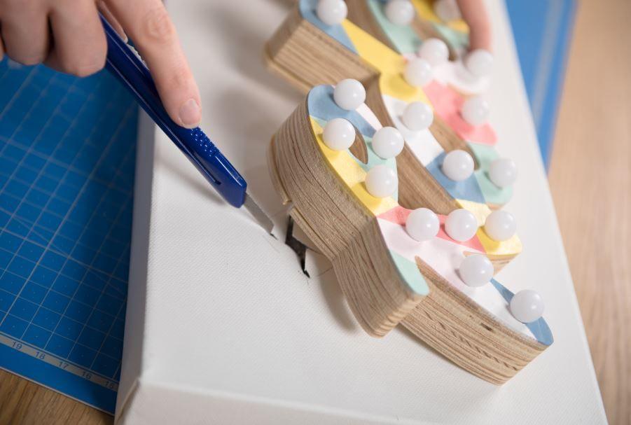 8. Positionner le mot « Happy » sur la toile et faire une entaille à l'aide d'un cutter au niveau de la lettre « Y » pour pouvoir y glisser le boîtier de commande. Enduire de colle l'arrière du mot, insérer le boîtier de commande dans l'entaille et le fixer au dos de la toile à l'aide des pastilles adhésives. Coller le mot à la toile.