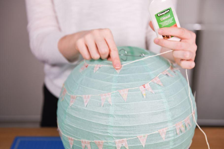4. Fixer en biais la guirlande ainsi obtenue tout autour de la boule en papier avec des points de colle vinylique.