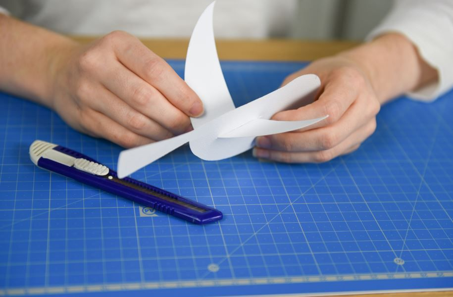 2. Faire une entaille au niveau du dos de l'oiseau en papier avec un cutter et y glisser les ailes. Pour donner du mouvement, marquer un pli pour que les ailes de l'oiseau en papier remontent. Répéter ces deux étapes pour créer une dizaine d'oiseaux en papier.