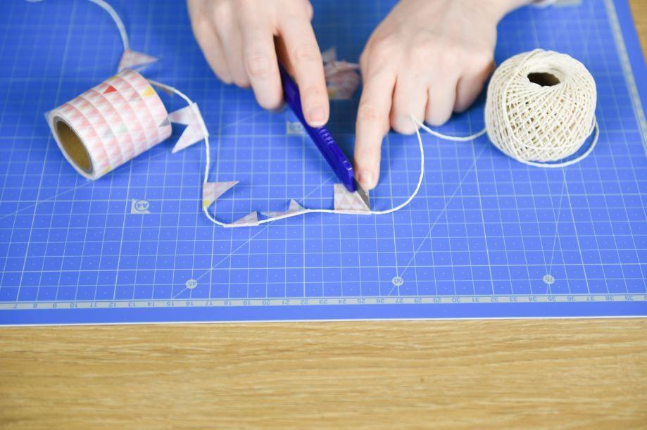 3. Découper un morceau de masking tape de la collection. Le plier en deux sur la ficelle. Couper l'extrémité du morceau de masking tape avec un cutter dans la forme souhaitée (triangle, flèche...) Répéter cette étape sur 1,50 m de ficelle environ.