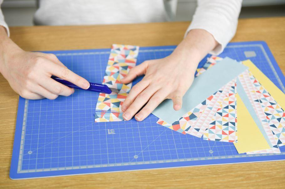 5. Découper une vingtaine de bandes de 5 x 20 cm dans les papiers origami de la collection. Pour chaque bande, couper des franges à l'aide d'un cutter sur toute la largeur en laissant une zone de 1 cm non découpée sur la partie haute.