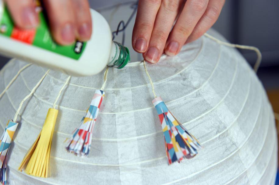 7.Après avoir créé une vingtaine de pompons, les fixer au sommet de la boule en papier avec des points de colle vinylique. Jouer sur la longueur des ficelles pour créer du relief.