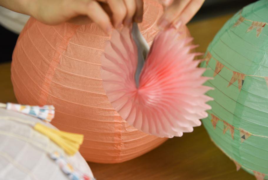 8. Composer la suspension en fixant à différentes hauteurs avec du fil de nylon les boules en papier préalablement décorées. Animer la composition en ajoutant des fleurs et des oiseaux en papier.