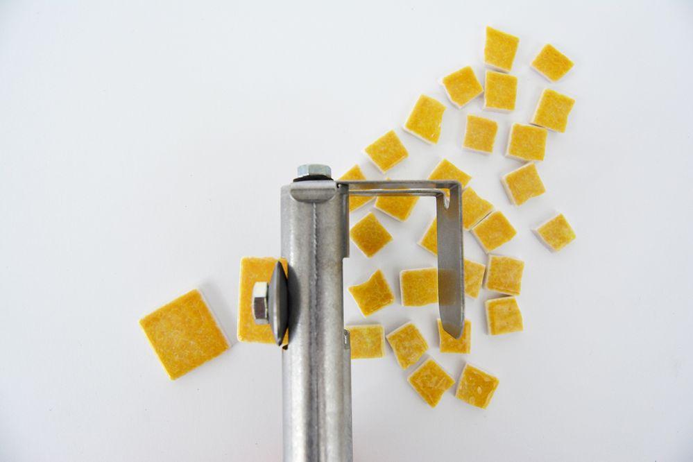 2. Couper des petits carrés de mosaïque. Choisir les tesselles jaune foncé pour l'écorce de la rondelle de citron. Positionner votre pince mosaïque Zag-Zag au centre de la tesselle, positionner la main le plus loin possible sur le manche et presser pour couper en deux le carré émaillé. Recommencer cette action dans les deux moitiés obtenues. Répéter cette action sur 7 autres tesselles du même coloris pour réaliser le contour de la rondelle.