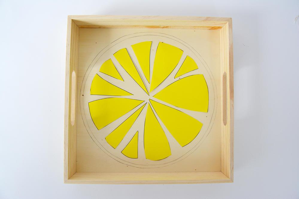 1. Télécharger et imprimer le gabarit. Découper le rond, le positionner sur le fond du plateau et marquer les contours avec un crayon à papier. Répéter cette action avec le rond inférieur et les parties jaunes.
