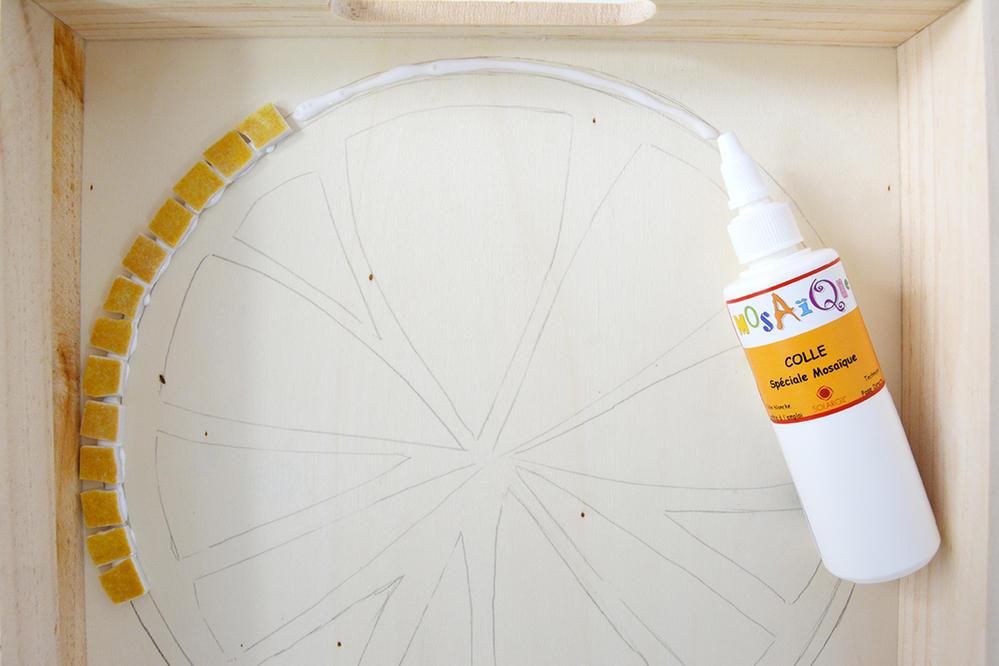 3. Déposer un liseré de colle sur le contour de la rondelle de citron. Coller un à un chaque petit carré en suivant votre dessin au fond du plateau.