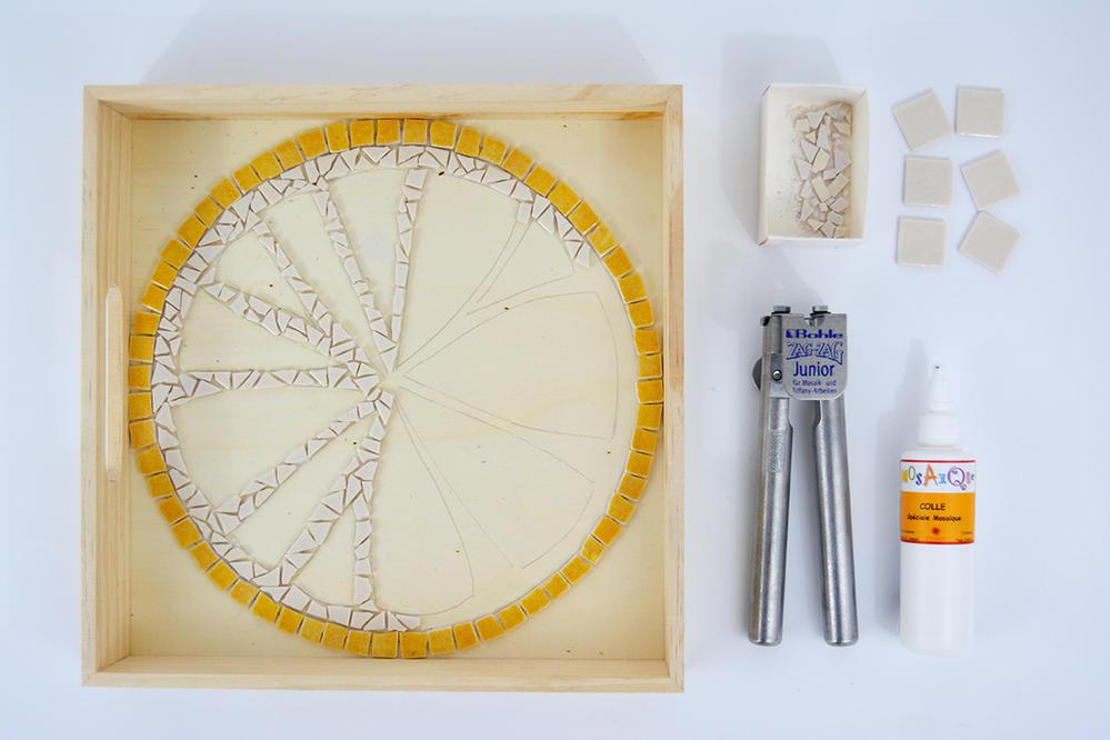 4. Poursuivre la découpe des tesselles blanches. Découper les tesselles en plusieurs formes à l'aide de la pince Zag Zag, toujours en positionnant la pince au milieu de chaque morceau découpé.  Enduire de colle mosaïque la surface  dessinée et coller chaque morceau. Conseil : Pour un joli rendu, serrer et imbriquer au  plus près  chaque pièce découpée en laissant un espace très fin entre chaque.