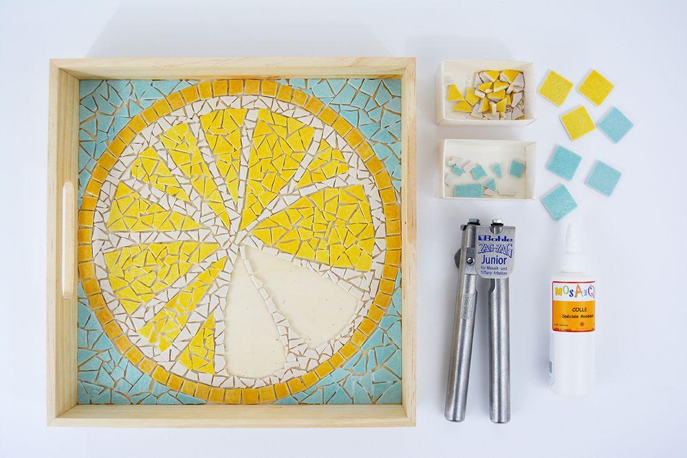 5. Poursuivre la découpe des tesselles jaune vif et bleu clair. Astuce : commencer par coller les morceaux pour marquer le contour des formes à remplir.