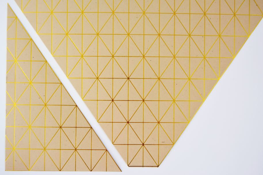 2. Découper un triangle droit dans le papier graphique kraft en suivant les lignes dorées.