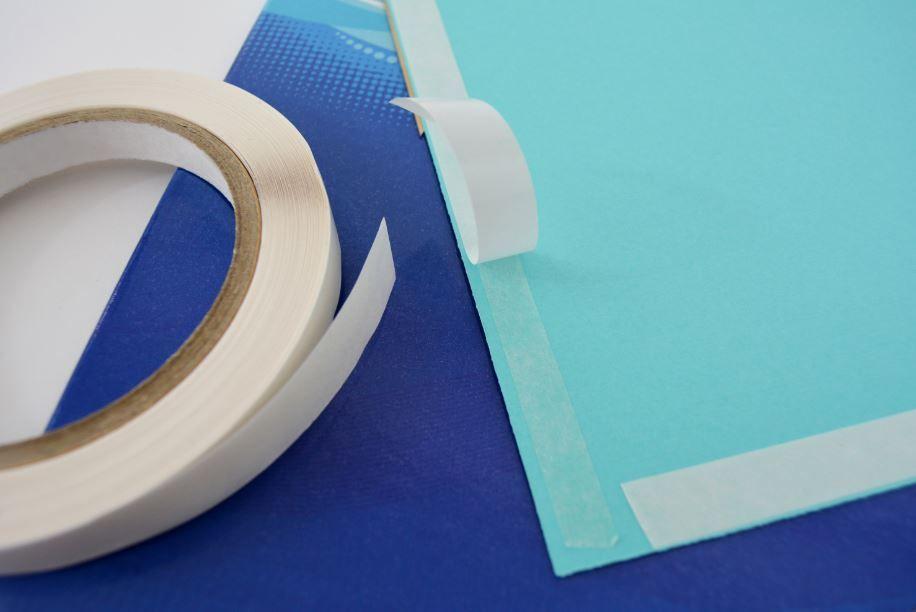 7. Coller le double-face au dos des rectangles et de la bande de 5 cm. Décoller la partie blanche et fixer le rectangle de couverture et le dos uni sur le cahier. Fixer la bande sur le côté gauche de la page de couverture et la rabattre au dos en suivant le pli du cahier. Avec les ciseaux, arrondir les angles des rectangles en suivant l'arrondi du cahier. Astuce : insérer le cahier dans un protège-cahier transparent.