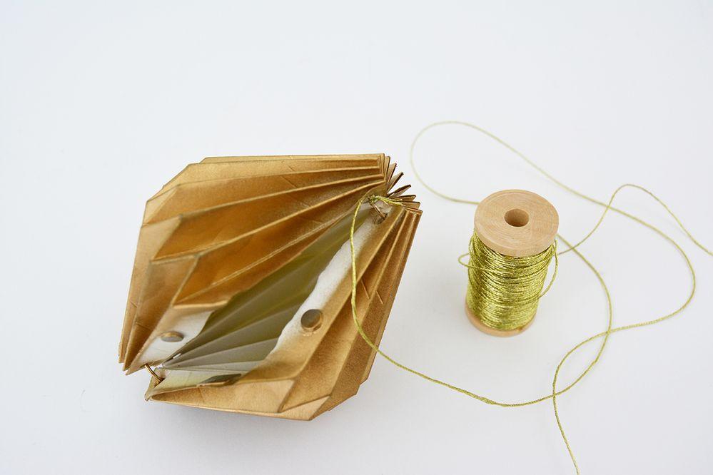 2. Pour créer une suspension, couper une longueur de ficelle dorée et les fixer à l'extrémité haute de chaque toupie.