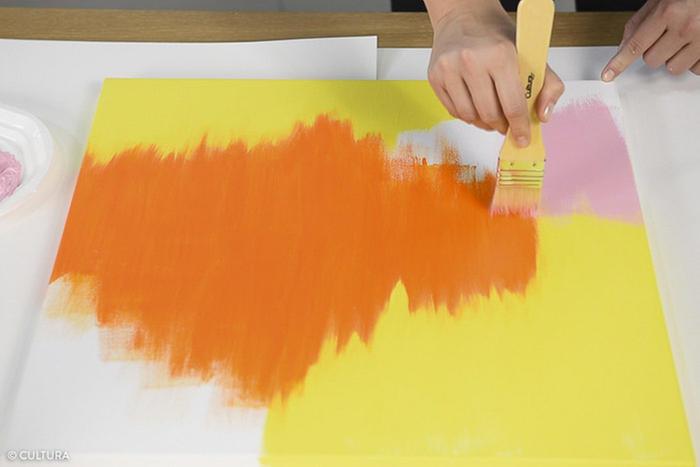 1. Peindre les différentes parties du fond de la toile avec les mélanges de couleurs obtenus précédemment à l'aide d'un spalter. Pour créer l'effet « brush », effleurer les zones à peindre avec le spalter enduit de peinture pour marquer les traces de pinceaux. Conseil : commencer par peindre les couleurs les plus claires : jaune, orange et rose. Laisser sécher entre chaque coloris pour créer des zones franches.