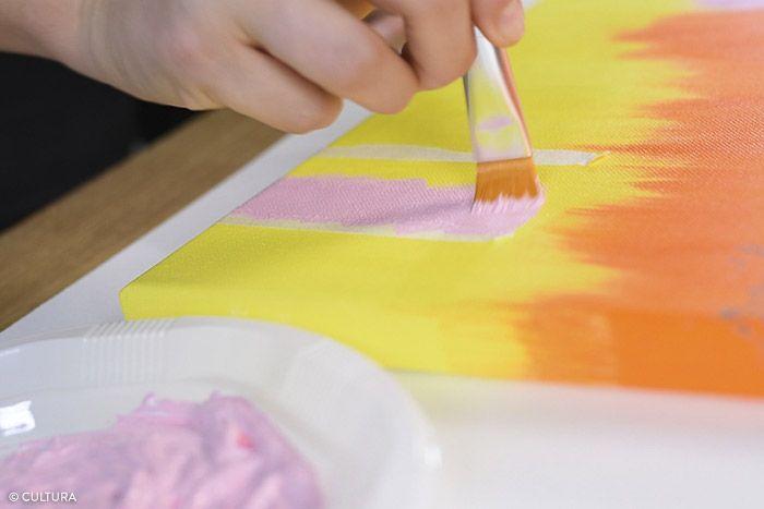 4. Pour créer deux bandes irrégulières en bas de la toile, déchirer en deux le ruban de masquage sur sa longueur et délimiter les zones à peindre. Appliquer le coloris rose à l'aide d'un pinceau plat. Laisser sécher. Appliquer une seconde couche si nécessaire. Laisser sécher. Retirer le ruban de masquage pour découvrir l'effet « déchiré ».