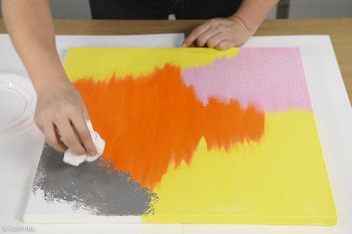 3. Déchirer une longueur d'essuie-tout et le froisser entre les mains. Le tremper dans la peinture acrylique gris neutre et le tamponner sur la toile. L'enduire de peinture autant que nécessaire pour créer l'effet texturé sur toute la zone définie en haut de la toile. Laisser sécher.