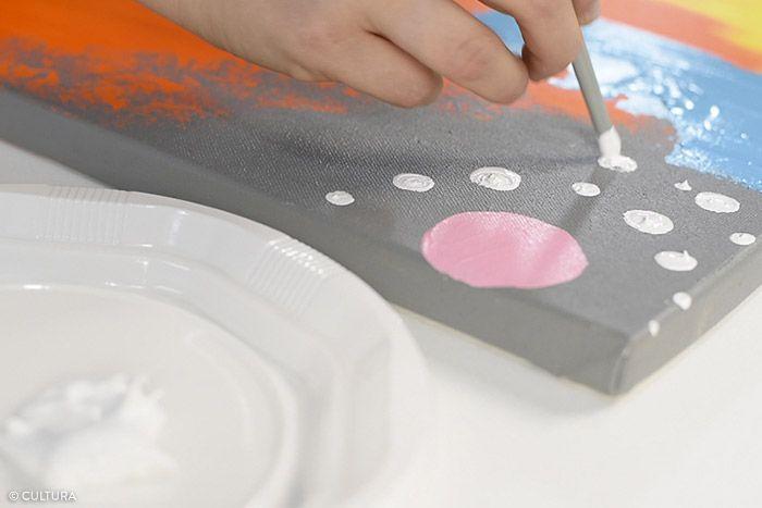9. Peindre un rond rose en haut de la toile. Enduire l'extrémité du manche d'un pinceau de peinture acrylique blanc et dessiner des cercles de points plus ou moins gros sur la zone définie. Laisser sécher. Répéter cette action avec le mélange de peinture coloris jaune vif sur la zone définie. Laisser sécher.
