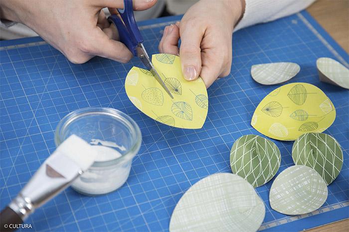 3- Pour donner du relief, inciser la base des feuilles sur 1 cm à l'aide des ciseaux. Poser un point de colle sur la base de la partie gauche entaillée et positionner dessus la base de la partie droite entaillée. Laisser sécher. Répéter cette action pour toutes les feuilles.