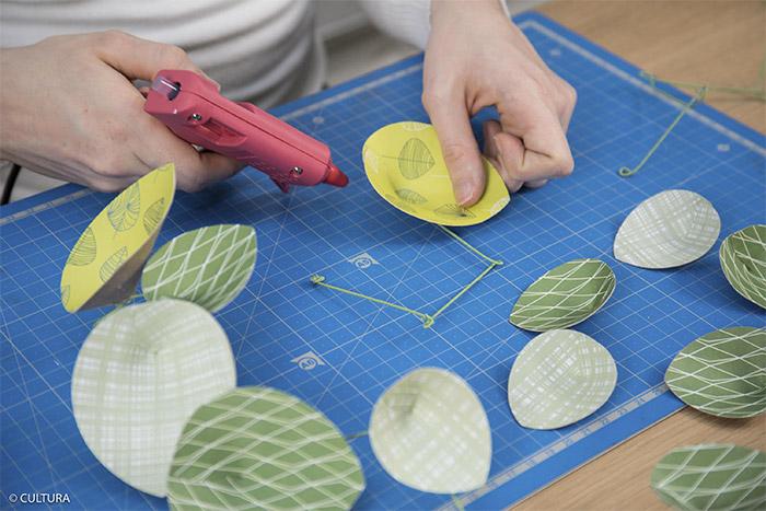 6- Coller les feuilles de la plante sur chaque boucle des fils à lier à l'aide du pistolet à colle. Répartir harmonieusement les couleurs et les imprimés. Laisser refroidir.