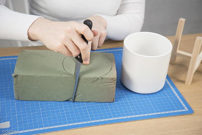 7- Reporter la circonférence du pot en porcelaine sur le bloc de mousse pour composition florale. Découper à l'aide d'un couteau et insérer dans le pot.