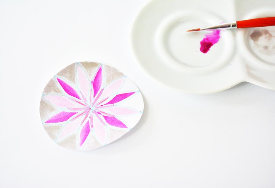 6.  Télécharger le gabarit de la rosace. L'imprimer sur une feuille du bloc de papier. Peindre les deux côtés de la rosace en marquant la base du motif avec le marqueur drawing gum. Peindre la rosace en mixant les couleurs et les effets de peinture. Après séchage complet, frotter doucement le drawing gum avec le doigt.
