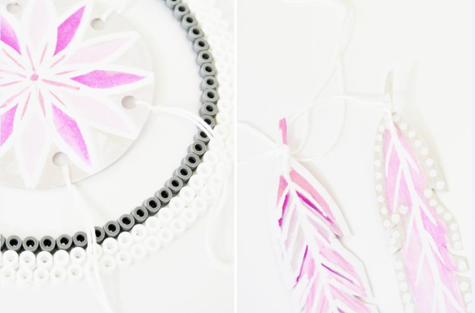 8. Créer six trous autour de la rosace à l'aide d'une perforatrice. Attacher le centre de l'attrape rêve à l'aide de fils tendus autour du cercle en perles à repasser. Couper différentes longueurs de fils et nouer une à une les plumes en papier à chaque extrémité. Ajouter un point de colle sur la plume pour consolider le noeud. Harmoniser la disposition en attachant plusieurs plumes de différentes tailles au cercle.