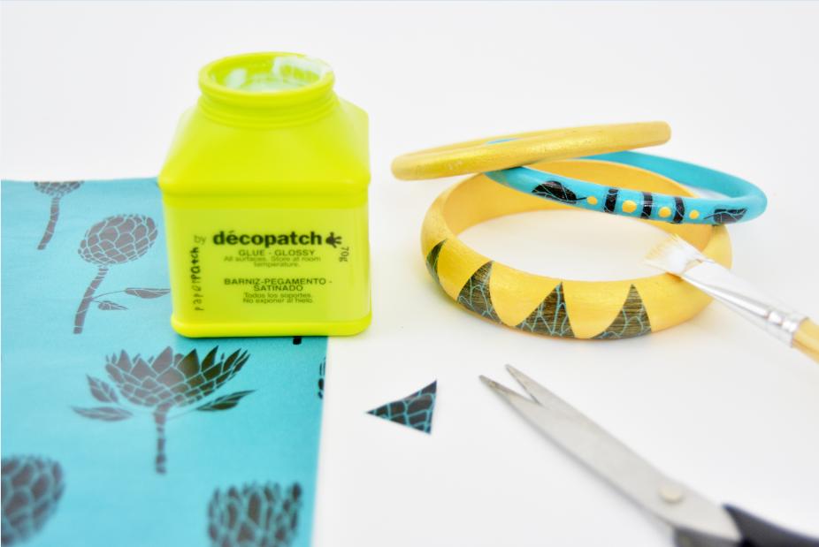 Idée n°2 : 4. Peindre les bracelets en coloris or ou bleu turquoise. Laisser sécher. Découper des formes graphiques dans les motifs du papier décopatch® choisi et décorer les bracelets en suivant la technique de collage expliquée précédemment.