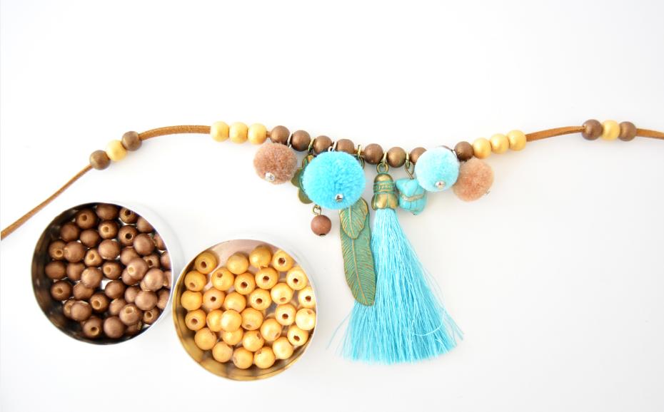 2. Démonter le pendentif à breloques et insérer sur la longueur de suédine chaque breloque et pompons alterné de perles coloris chocolat nacré. Poursuivre le montage par 3 perles dorées de chaque côté puis mixer les coloris de perles pour poursuivre le sautoir.