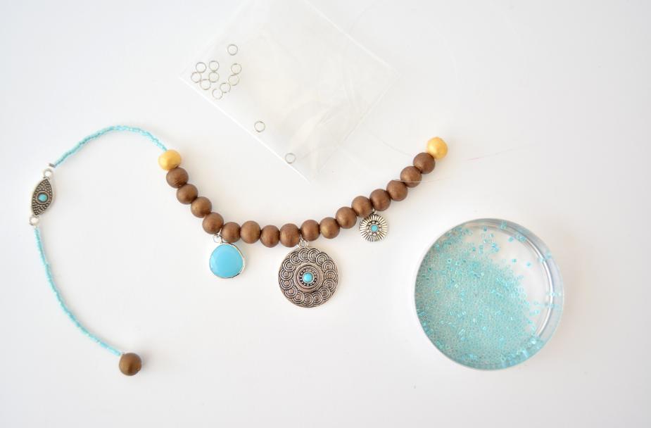 5. Enfiler une perle dorée à la suite des perles miyuki et la bloquer en créant une boucle avec le fil nylon dans le trou de la perle. Insérer 4 perles coloris chocolat nacré, une nouvelle breloque, 4 autres perles puis le médaillon central. Répéter cette étape à l'inverse sur l'autre côté du médaillon pour créer la symétrie.