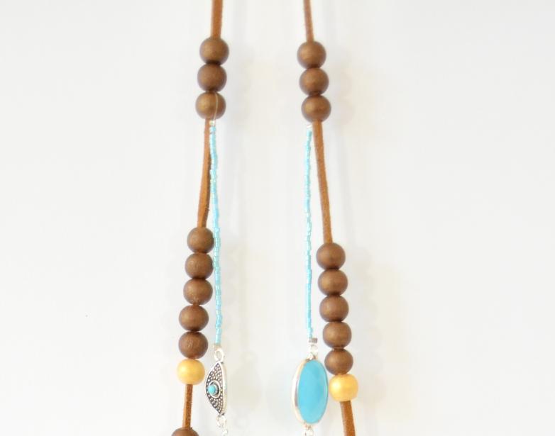 7. Insérer la seconde partie du collier sur la suédine à l'aide des perles rondes aux extrémités. Placer de part et d'autre de la suédine 2 autres perles coloris chocolat avant de nouer la suédine pour fermer le sautoir.