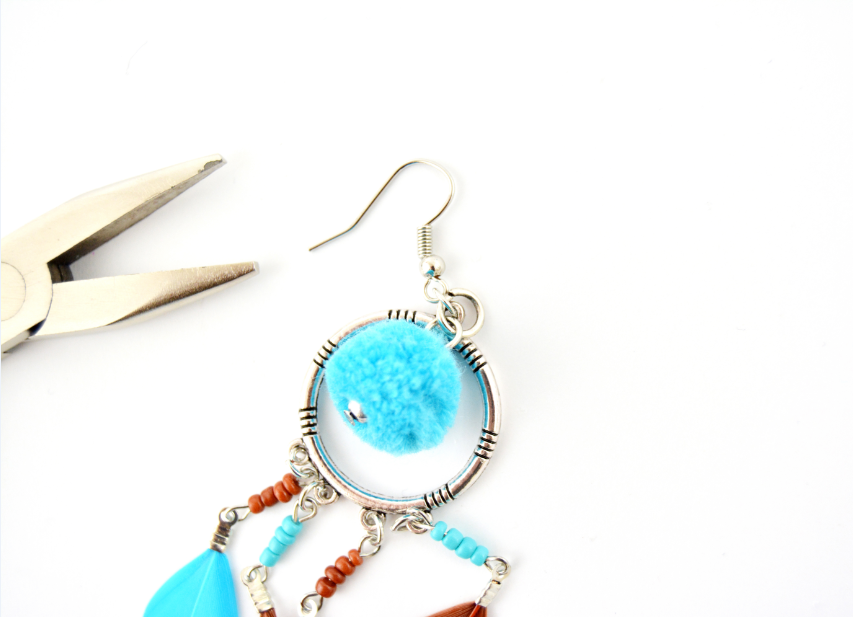 3. Fixer un pompon bleu sur l'anneau supérieur du pendentif.