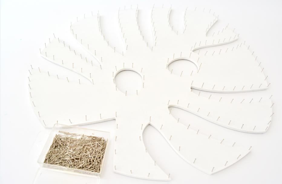 2. Clouter les épingles à égales distances sur le contour du support et des formes perforées à l'aide d'un petit marteau.