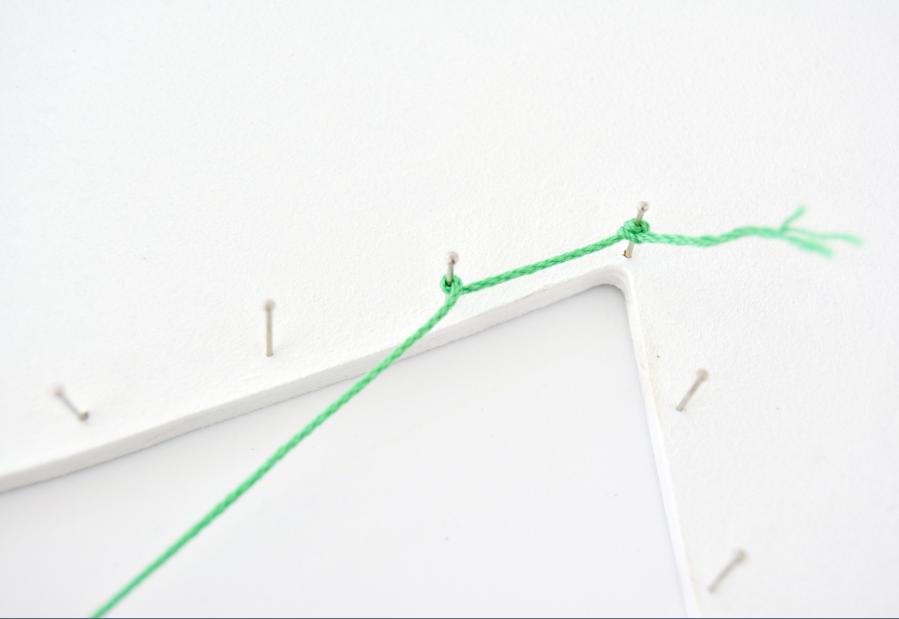3. Nouer la ficelle à une épingles puis enrouler sur les suivantes le fil pour le maintenir. Réaliser d'autres nœuds si besoin.