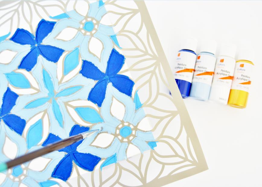 3. Eclaircir la peinture coloris bleu marine (1/2) de blanc (1/2) pour créer une 3ème tonalité de bleu. Peindre délicatement les différentes parties du pochoir avec les trois coloris de bleus et la peinture dorée en tapotant à la verticale avec le pinceau pour éviter tout débords de peinture. Laisser sécher et passer une seconde couche si nécessaire.
