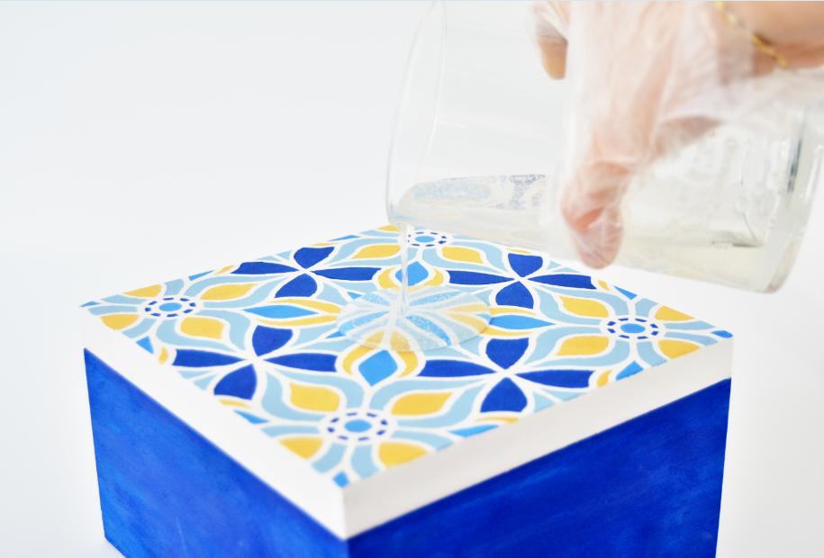 6. Couler délicatement la résine de glaçage sur le couvercle de la boite.