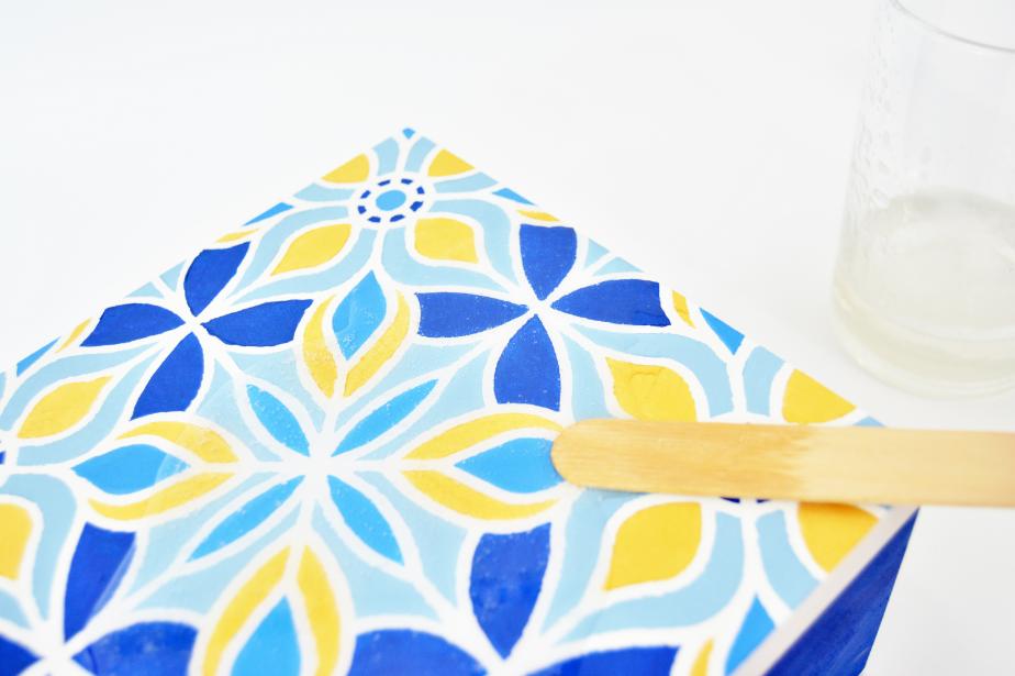 7. Etirer la résine de glaçage jusqu'aux bords de la boite à l'aide de la spatule en bois fournie. Laisser sécher à l'abri de la poussière pendant 24 h. Astuce : chasser les bulles d'air à l'aide de cure-dents.