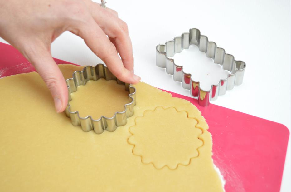 2. Utiliser les emporte-pièces cannelés rond et rectangulaire pour découper les biscuits dans la pâte.