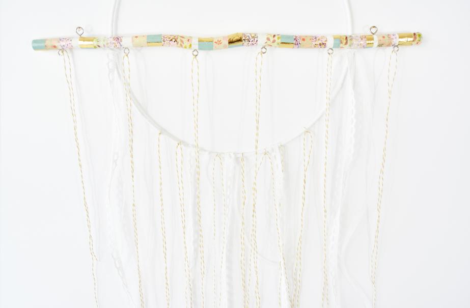 7. Couper différentes longueurs de ficelle et rubans et les nouer au support et au anneaux de la branche.