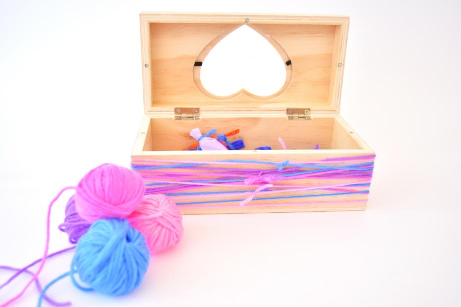 8. Enrouler le bas de la boîte de longueurs de fil de laine pour créer un rendu graphique. Nouer les deux extrémités de chaque fil au centre de la boîte. Garnir la boîte des magnets surprises.