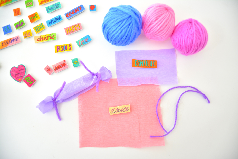 7. Pour emballer chaque magnet, découper des morceaux de papier crépon de différentes couleurs. Nouer chaque extrémités avec un morceau de fil de laine pour former des petits « crackers » colorés.