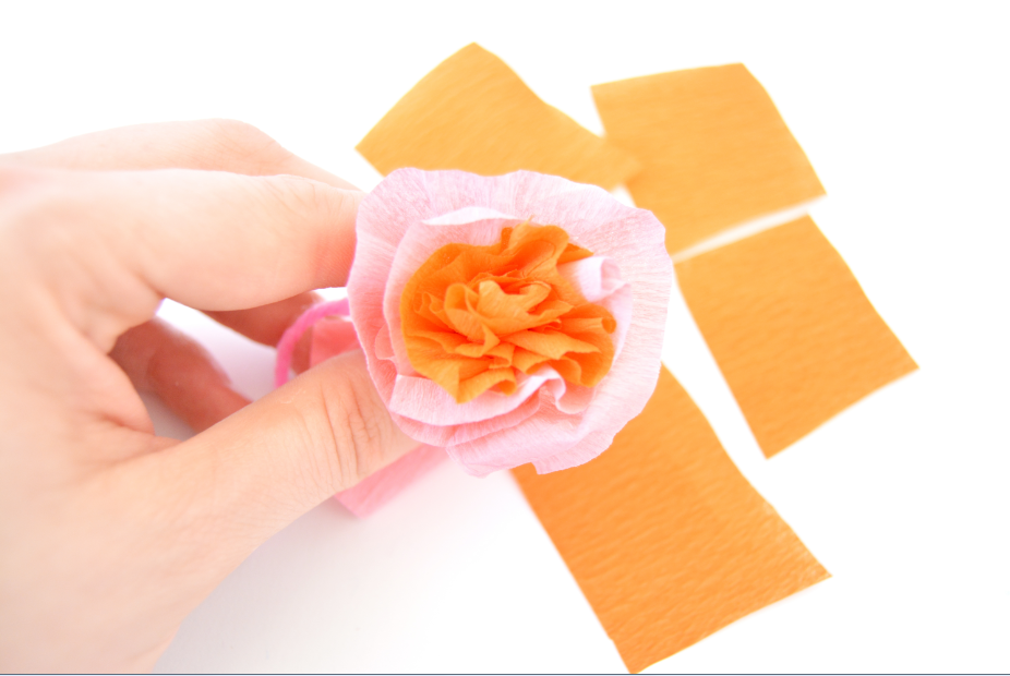 9. A l'aide de rectangles découpés dans le papier crépon orange et rose, les enrouler sur eux-mêmes et les superposer pour former une fleur. Nouer l'ensemble avec un fil de laine pour maintenir les pétales. Couper l'excédent.
