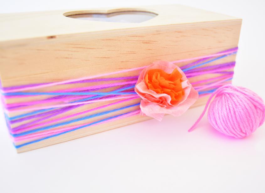 10. Coller la fleur au centre de la boîte pour cacher les noeuds des fils de laine.