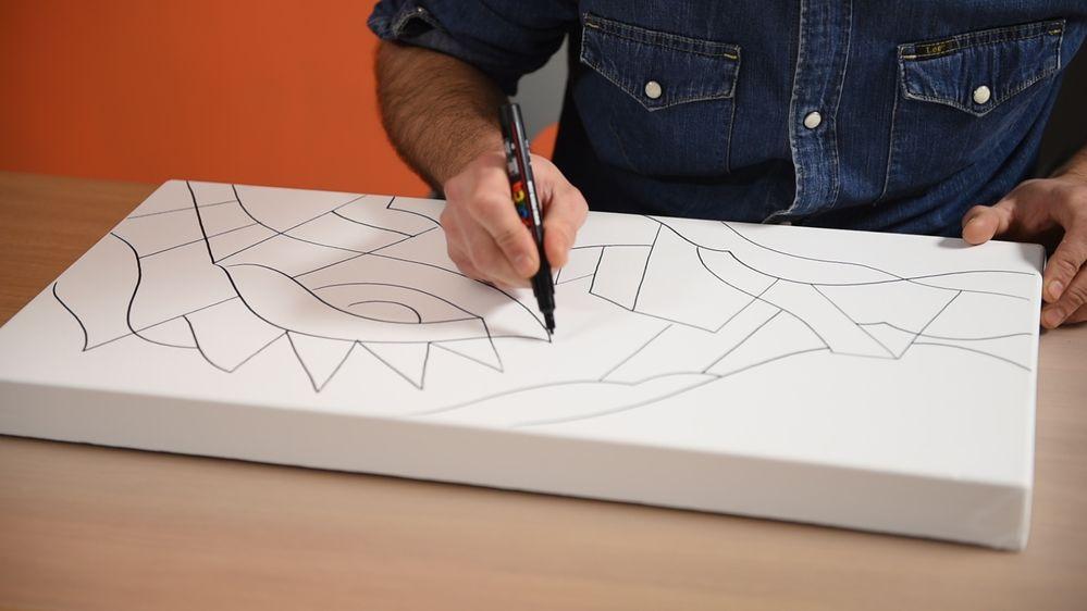 1. Amorçage des marqueurs POSCA : Agiter fermement le marqueur, capuchon fermé, pour faire circuler la bille contenue à l'intérieur. Sur une feuille de papier, appuyer la pointe à plusieurs reprises, afin d'imbiber cette dernière de peinture. Bien refermer le marqueur avec le capuchon après usage. Sur la toile de coton 3D, format 30 x 60 cm, tracer les contours du motif au marqueur Posca coloris Noir (pointe moyenne 2,5 mm ) en s'inspirant du schéma à télécharger. Dessiner aussi les traits sur les côtés de la toile. Laisser sécher.