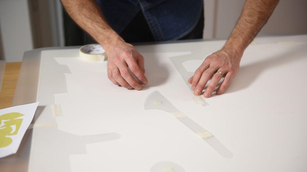3. Positionner le pochoir sur la toile coton 60 F, comme présenté sur le schéma ci-dessous. Fixer le tout avec du ruban de masquage. Astuce : Pour fixer les formes intérieures du pochoir, créer du double-face en collant sur eux-mêmes des morceaux de ruban de masquage.