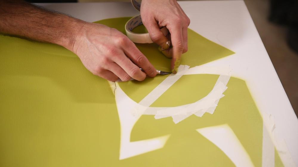 5. Délimiter les différentes zones à peindre à l'aide du ruban de masquage en s'inspirant des schémas ci-dessous. Utiliser le cutter de présicion pour arrondir les formes. Important : Ne pas appuyer fortement avec la lame du cutter au risque de couper la toile. Autour de chaque zone à peindre, positionner et fixer avec du ruban de masquage des feuilles A4 pour protéger la toile des retombées de peinture. Peindre les zones délimitées avec le spray de peinture Montana Gold Acrylic coloris Shock Orange Dark. Laisser sécher. Retirer le ruban de masquage et les feuilles de protection.