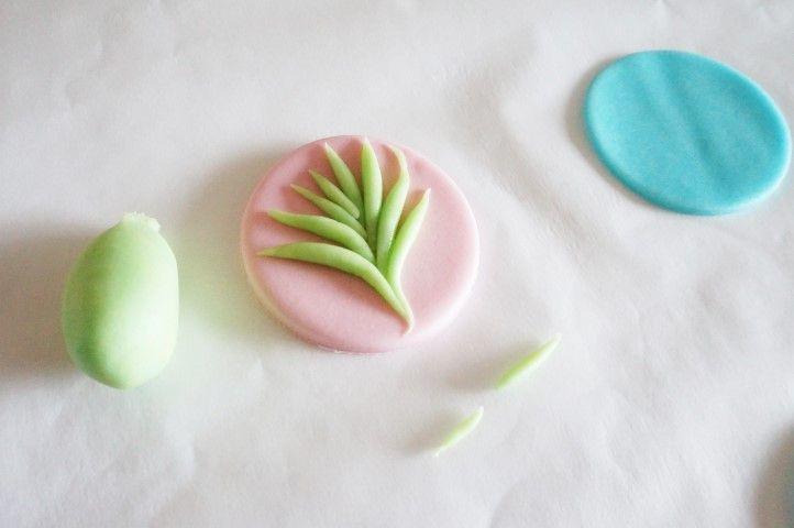 5. Mélanger la pâte à sucre jaune à la bleue pour obtenir un vert. Modeler entre les mains de fines branches pour créer un motif végétal sur certains sablés.