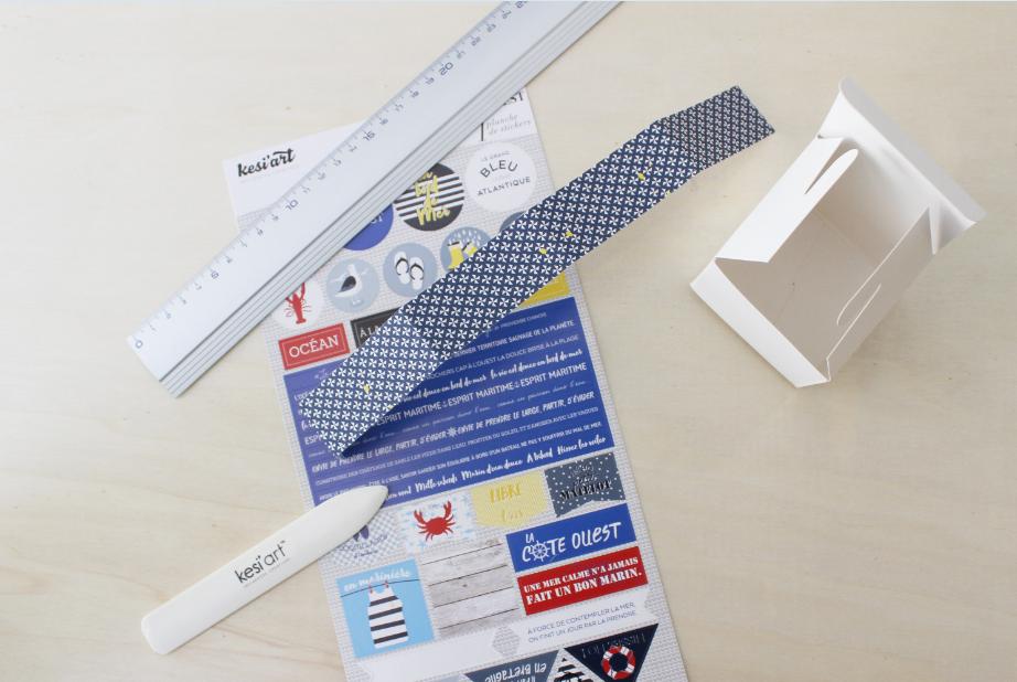 1. Les boîtes Plier et assembler les boîtes pré-pliées. Découper 4 bandes de 3 cm x 30 cm dans 4 papiers imprimés Grand Ouest. Plier à 7 cm, à 14 cm, à 21 cm puis à 28 cm.