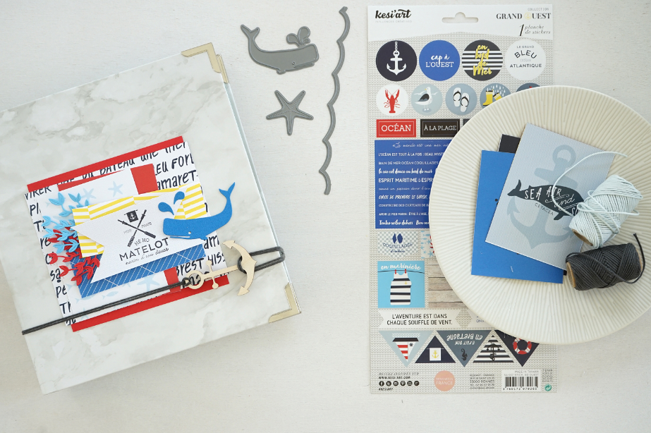 3. Superposer 2 étiquettes du papier Ouessant sur le rectangle de papier précédemment collé sur la couverture. Ajouter une bande de papier de 10 x 5 cm et de papier imprimé de la même taille. Glisser dessous deux découpes réalisées avec les dies au choix. Ajouter le fanion et une autre découpe bord de mer.